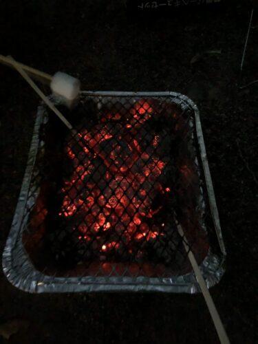 暗い中、炭の火力を確認している