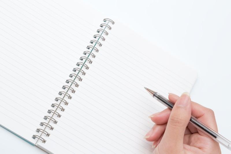 ノートとペンをもつ手